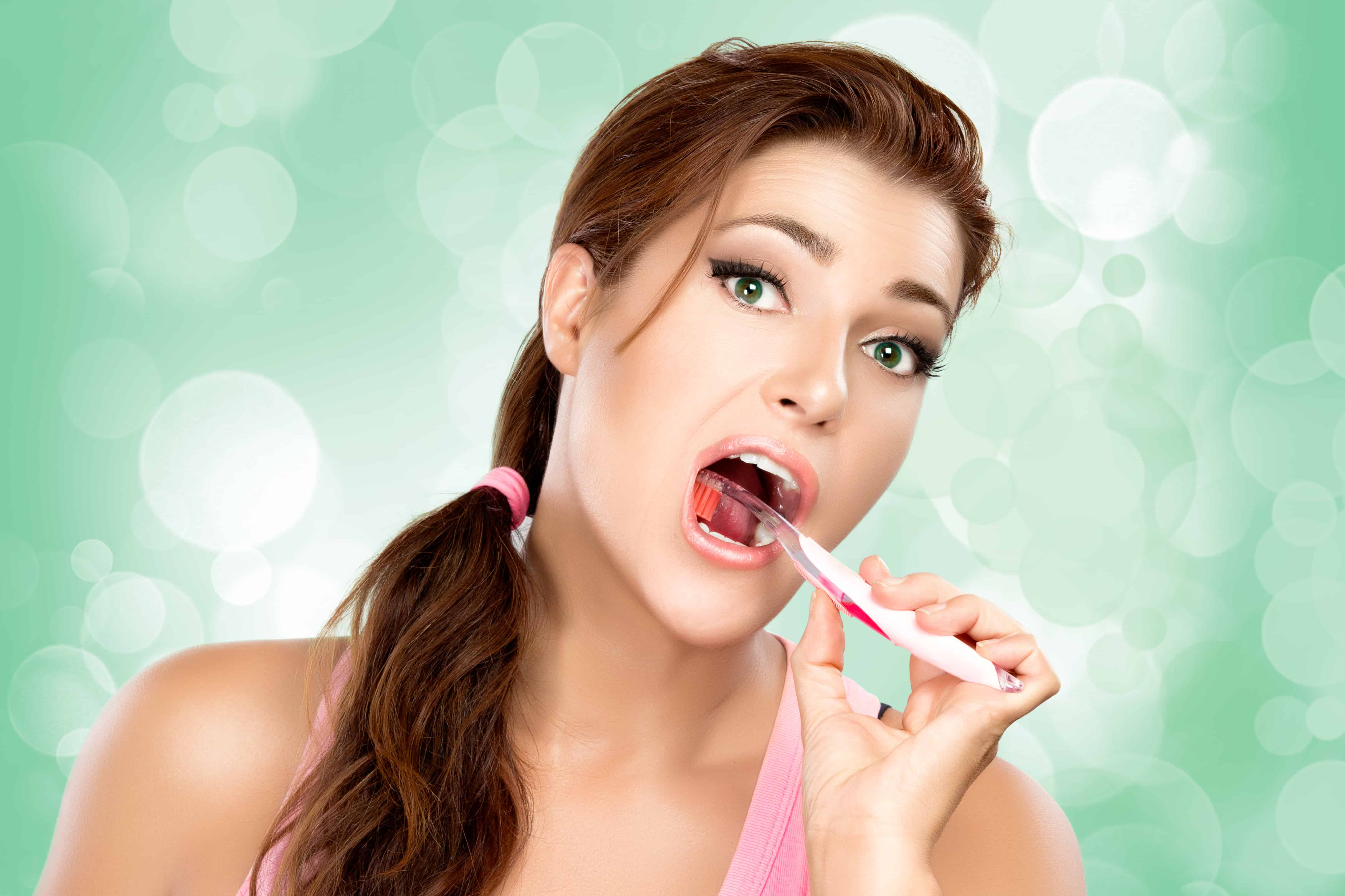 Beauty and funny young woman brushing teeth with comical expression