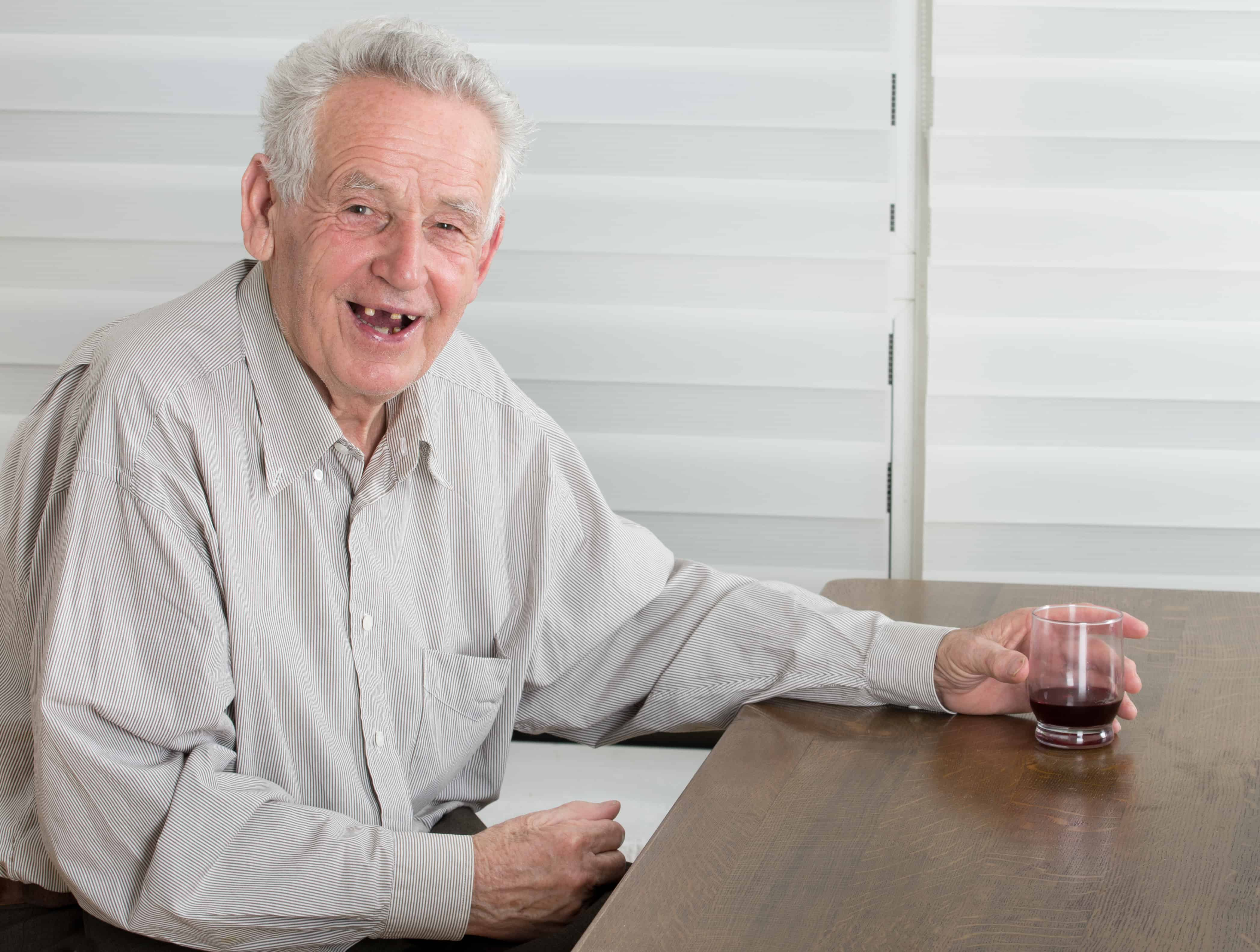 Old man holding glass with alcohol dring and laughing laudly