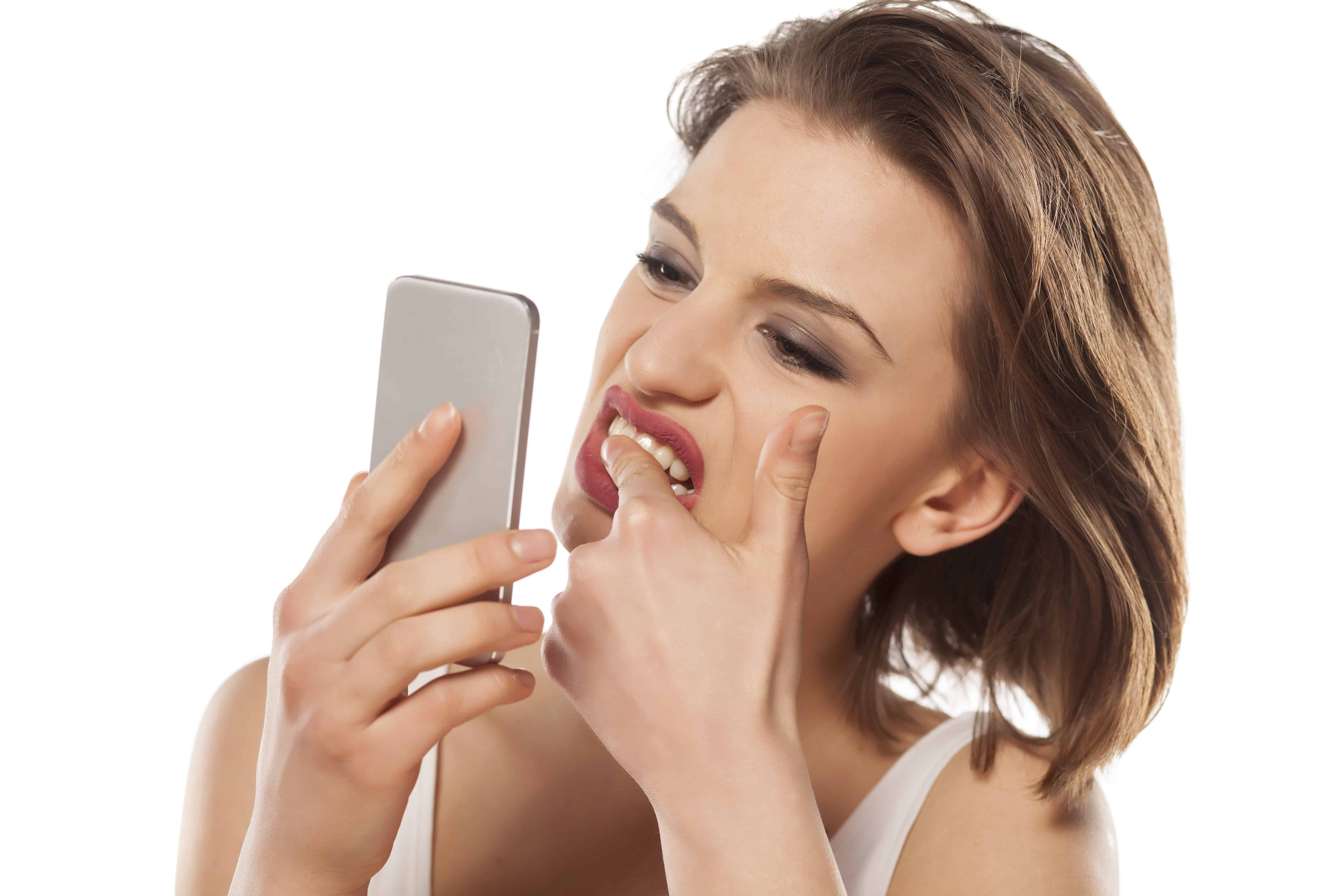 girl cleans stains on her teeth looking in the smartphone